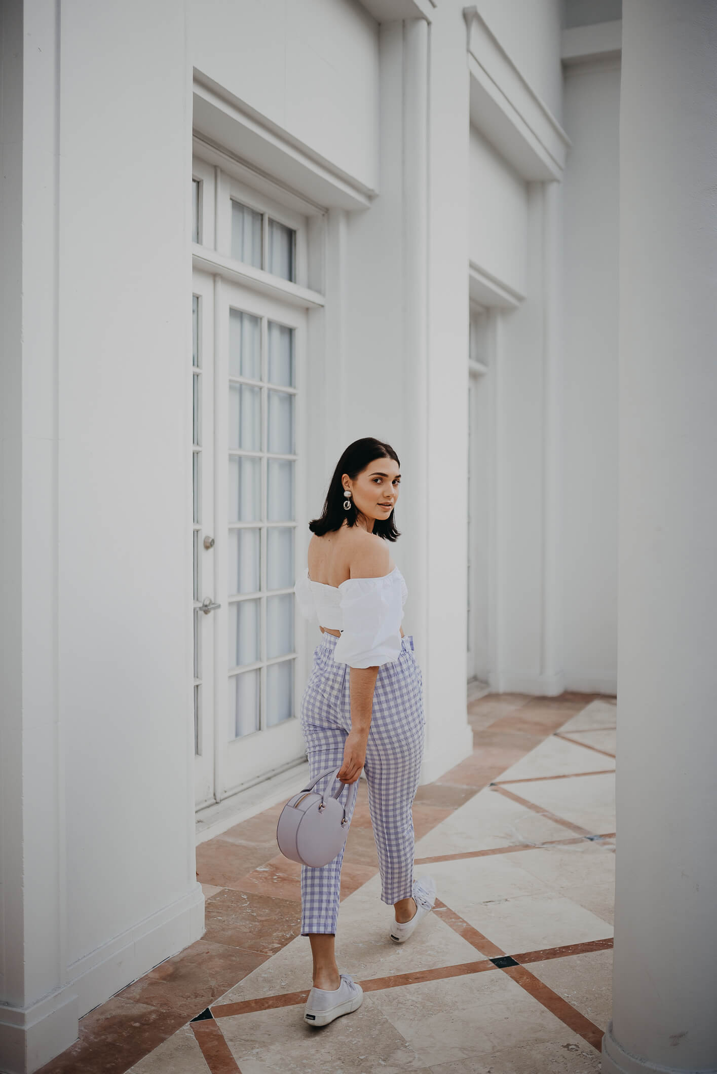 look primavera con pantalón a cuadros de color lila, un top blanco con hombros al aire y una carterita lila